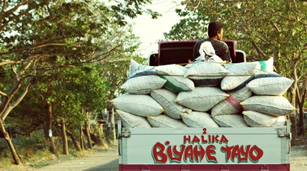 """Man riding on rice truck that says, """"Come, travel with us."""""""
